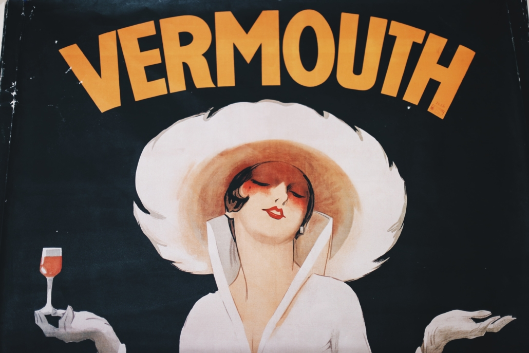 A vintage photo showing a woman holding a liqueur called vermouth. Vermouth can be a sweet or dry liqueur.